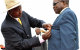 Minister Muruli Mukasa receiving a medal while KamandaBataringaya waits for his
