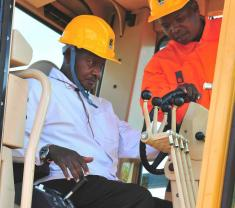 President Yoweri Museveni operating a tractor at the commissioning of Arua-Vura-